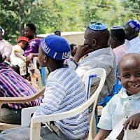 Des membres de la communauté juive ougandaise Abayudaya écoutent leur chef religieux dans un village à côté de Mbale, à l'est de l'Ouganda, le 2 juillet 2016 (Crédit :  AFP/Michael O'Hagan)