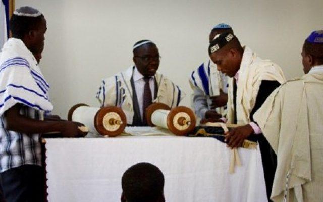 Le rabbin Gershom, second à gauche, se prépare à la lecture de la Torah pendant un service du Shabbat au sein de la communauté juive  Abayudaya dans un village proche de Mbalé, à l'est de l'Ouganda, le 2 juillet 2016 (Crédit : AFP/Michael O'Hagan)
