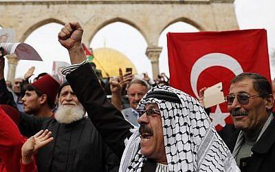 Des fidèles musulmans brandissent des drapeaux palestiniens et turcs après la prière du vendredi à la mosquée Al-Aqsa située sur le Mont du Temple dans la Vieille Ville de Jérusalem,  le 22 décembre 2017. (AFP Photo/Ahmad Gharabli)
