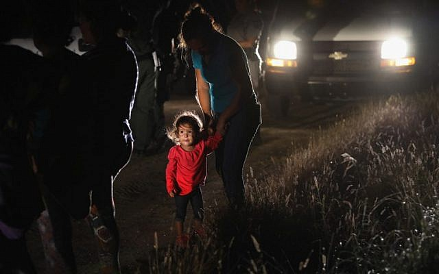 Une petite fille de deux ans originaire du Honduras avec sa mère après avoir été arrêtée par les agents de la police des frontières près de la frontière entre les Etats-Unis et le Mexique, à McAllen, au Texas, le 12 juin 2018 (Crédit : John Moore/Getty Images/AFP)