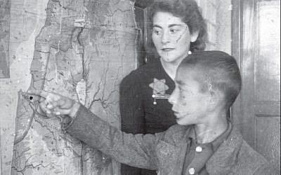 Une enseignante et son élève près d'une carte de la terre d'Israël au ghetto de Łódź, en Pologne (Crédit :  Yad Vashem Archives Collection)