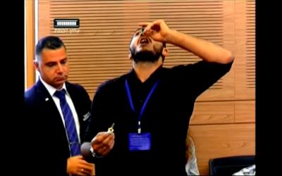Un homme avale une bouteille d'huile de cannabis pendant une réunion de la commission de la Santé à la Knesset (Capture d'écran)