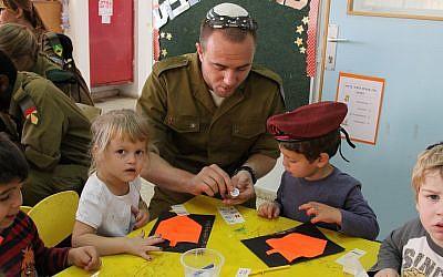 Un soldat du programme de conversion Nativ visite un jardin d'enfants dans l'implantation d'Efrat pour en apprendre davantage sur la fête juive de Hannukah, le 7 novembre 2013 (Crédit :  Gershon Elinson/FLASH90)