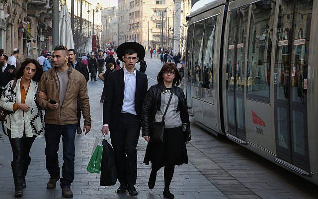 Un jeune couple laïque israélien marche à côté d'un couple ultra-orthodoxe alors que le tramway passe rue Jaffa dans le centre de Jérusalem le 22 janvier 2014. (Hadas Parush/Flash 90)