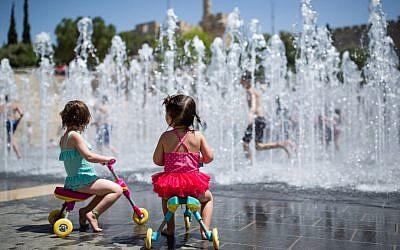 Des enfants jouent dans une fontaine, près de la Tour de David, dans la Vieille Ville de Jérusalem, le 17 avril 2016. (Crédit : Corinna Kern/Flash90)