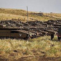 Des soldats israéliens devant des tanks près de la frontière israélo-syrienne sur le plateau du Golan, le 10 mai 2018 (Crédit : Basel Awidat/Flash90)