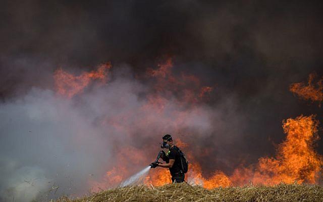 Les pompiers éteignent un feu dans un champ de blé qui avait été allumé par des cerfs-volants incendiaires depuis la bande de Gaza en Israël, le 30 mai 2018 (Crédit : Yonatan Sindel/Flash90)