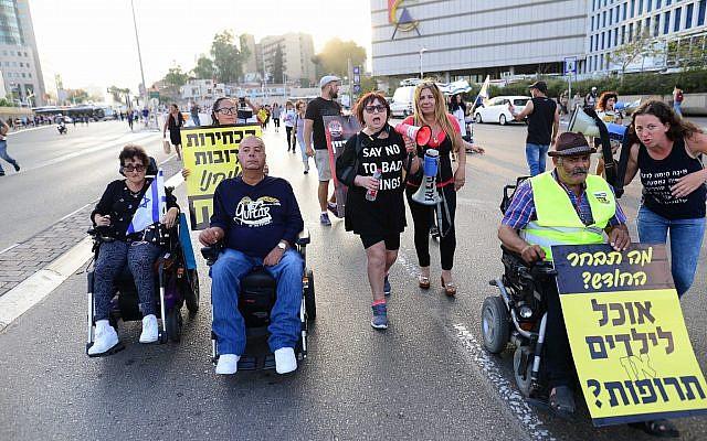Des personnes handicapées, des invalides et des activistes bloquent une route alors qu'ils prennent part à une manifestation pour réclamer de meilleurs soins de santé et de meilleures allocations à Tel Aviv le 31 mai 2018. (Photo : Tomer Neuberg/Flash90)