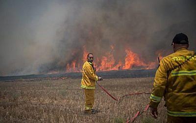 Des pompiers israéliens combattent un incendie dans un champ dans le sud d'Israël causé par des cerfs-volants incendiaires pilotés par des Palestiniens depuis la bande de Gaza le 5 juin 2018. (Crédit : Yonatan Sindel/Flash90)