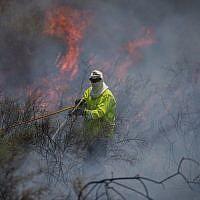 Des pompiers éteignent un incendie dans un champ causé par des cerfs-volants pilotés par des Palestiniens depuis la bande de Gaza, près de la frontière avec Israël, le 5 juin 2018. (Yonatan Sindel/Flash90)