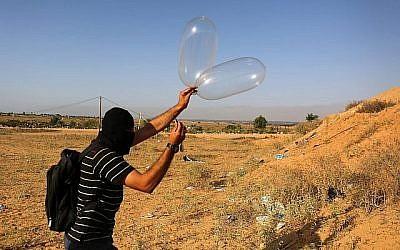 Un Palestinien prépare un ballon qui sera attaché à des matériaux inflammables puis sera envoyé par les airs vers Israël près de la frontière israélo-gazanaise, à Rafah, dans le sud de la bande de Gaza, le 17 juin 2018. (Abed Rahim Khatib/Flash90)
