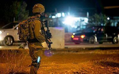 Des soldats israéliens se tiennent près du lieu d'une attaque présumée à l'entrée du village de Husan, en Cisjordanie, le 23 juin 2018. (Flash90)