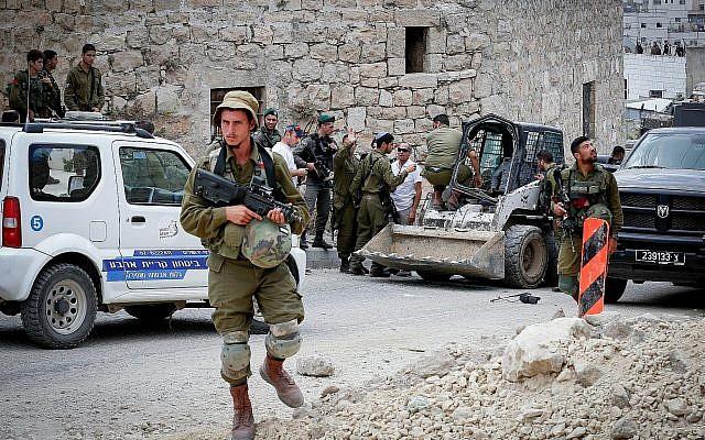 Les soldats israéliens sur les lieux d'une tentative d'attaque au véhicule-bélier dans la ville de Hébron, en Cisjordanie, le 2 juin 2018 (Crédit : Wisam Hashlamoun/Flash90)
