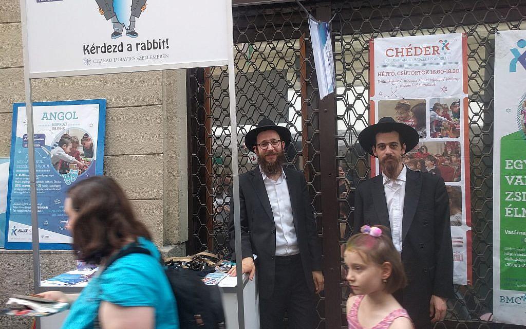 Les délégués Habad, les rabbins Yitzchak Stell, (à gauche), et Chaim Shaul Glitzinstein, proposent aux passants de prier et de mettre les phylactères au festival de rue Judafest à Budapest, le 10 juin 2018. (Yaakov Schwartz/ Times of Israel)