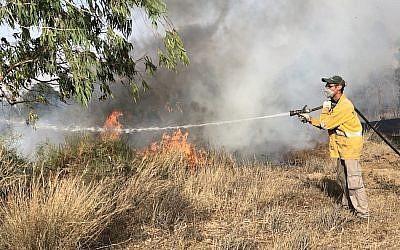 Un pompier éteint un incendie à la frontière israélienne avec Gaza, le 11 juin 2018. (Sam Sokol)