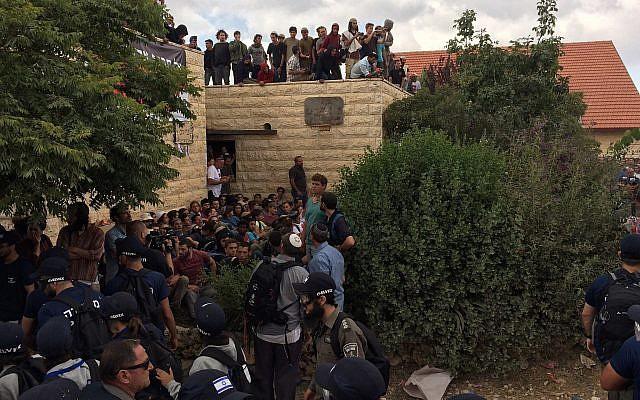 Des manifestants à l'avant-poste de Netiv Haavot dans la région du Gush Etzion en Cisjordanie pendant la démolition de l'une des 15 maisons construites illégalement, le 12 juin 2018. (Luke de Tress/Times of Israel)