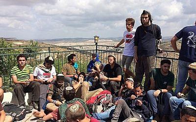 Des manifestants à l'avant-poste de Netiv Haavot, dans la zone du Gush Etzion en Cisjordanie, sur le toit d'une des 15 maisons construites illégalement peu avant leur démolition prévue, le 12 juin 2018. (Luke Tress/Times of Israel)