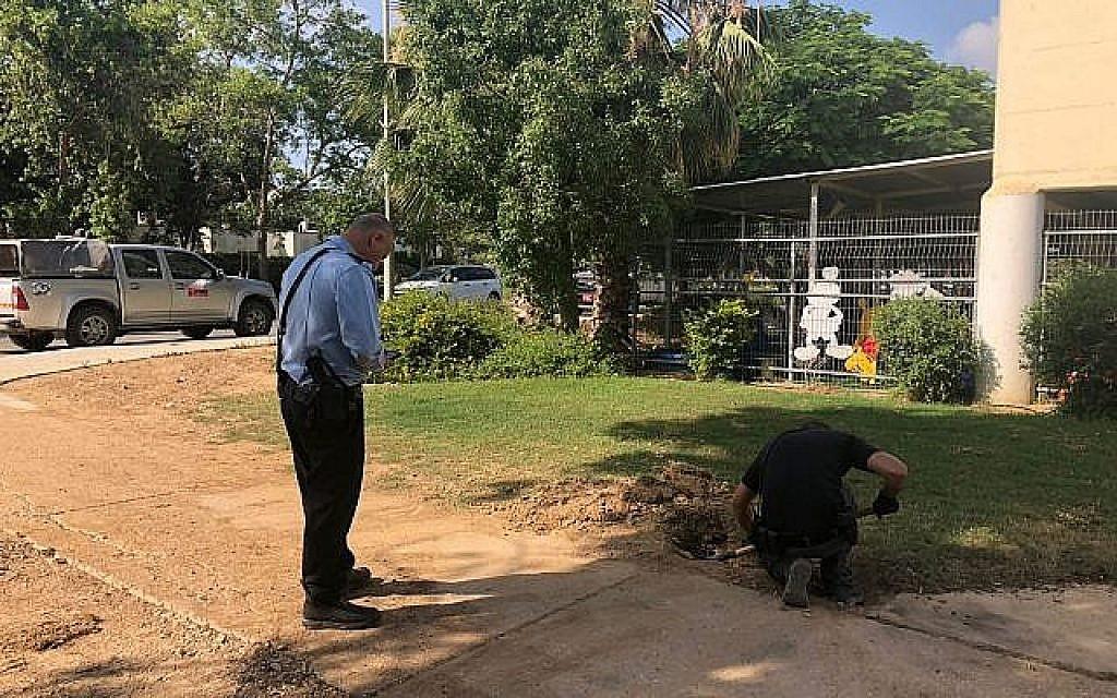 Un démineur déterre une roquette tirée depuis Gaza qui est tombée dans l'une des localités de la région d'Eshkol, près d'un jardin d'enfants, le 20 juin 2018 (Crédit: Région d'Eshkol)