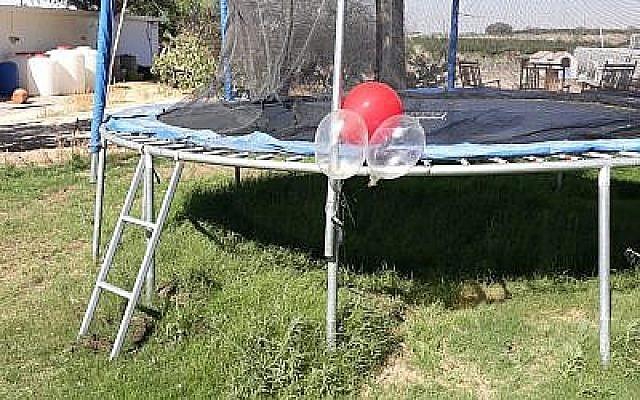 Un ballon sur lequel est fixé un petit engin explosif, qui s'est coincé sur un trampoline dans un jardin de la région d'Eshkol, dans le sud d'Israël, le 19 juin 2018. (Eshkol Security)