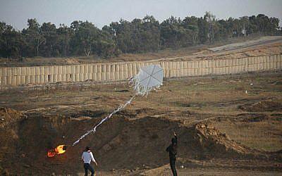 Deux Palestiniens font voler un cerf-volant incendiaire de la bande de Gaza vers le territoire israélien lors de manifestations de masse le long de la clôture de sécurité le 8 juin 2018. (Armée israélienne)