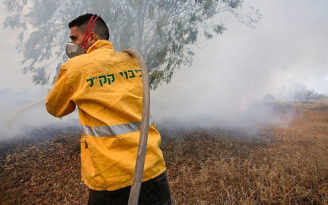 Un pompier du KKL-JNF tente d'éteindre un incendie dans le sud d'Israël, près de la frontière de Gaza, causé par des cerfs-volants incendiaires envoyés depuis la bande de Gaza. (Yehuda Peretz/KKL-JNF/Autorisation)