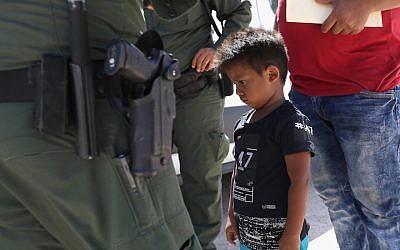 Un petit garçon du Honduras emmené en détention par des agents d'une patrouille de la police des frontières américaine près de la frontière entre les Etats-Unis et le Mexique, le 12 juin 2018 (Crédit :  John Moore/Getty Images)