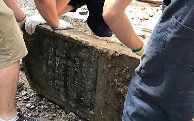 Des volontaires sauvent une pierre tombale juive utilisée pour paver une rue dans la ville de Lviv, l'une des 100 pierres tombales découvertes lors de travaux de voirie dans le centre de la ville en juin 2018. (Marla Raucher Osborn, Rohatyn Jewish Heritage/via JTA)