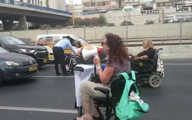 Plusieurs manifestants en fauteuil roulant ont bloqué l'autoroute Ayalon à Tel Aviv pendant une heure le 28 juin 2018. (Capture d'écran : Hadashot news)