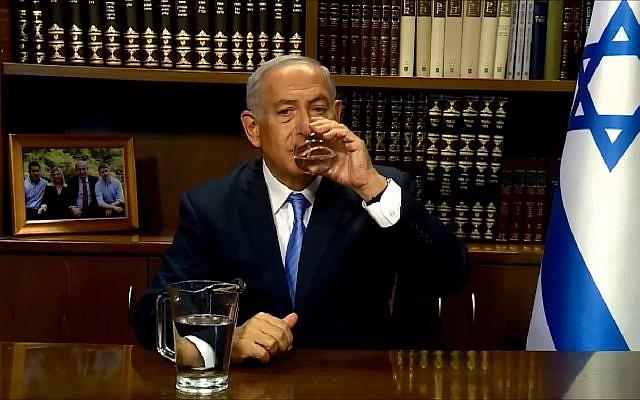 Le Premier ministre Benjamin Netanyahu boit un verre d'eau avant de s'adresser aux Iraniens sur la gestion de la sécheresse, le 10 juin 2018 (Capture d'écran : : YouTube)