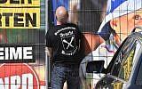 """Un gardien de sécurité privé avec """"la fraternité aryenne"""" sur son te-shirt ouvre la porte du lieu du festival néo-nazi  'Schild und Schwert' (bouclier et épétée) dans la petite ville d'Ostritz, à l'est de l'Allemagne, le 20 avril 2018 (Crédit :  AFP PHOTO / John MACDOUGALL)"""