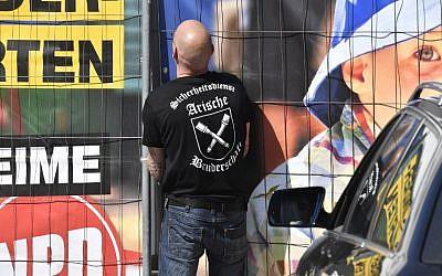 """Un gardien de sécurité privé avec """"la fraternité aryenne"""" sur son tee-shirt ouvre la porte du lieu du festival néo-nazi  'Schild und Schwert' (bouclier et épée) dans la petite ville d'Ostritz, à l'est de l'Allemagne, le 20 avril 2018 (Crédit :  AFP / John MACDOUGALL)"""