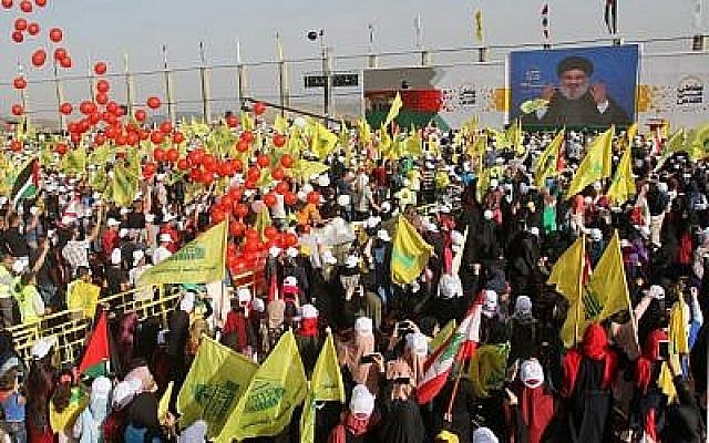 La foule brandit les drapeaux de l'organisation terroriste libanaise Hezbollah (jaune) et les drapeaux nationaux libanais lors de la Journée de Jérusalem dans le village de Maroun al-Ras, près de la frontière israélo-libanaise, le 8 juin 2018. (Crédit : AFP Photo/Mahmoud Zayyat)
