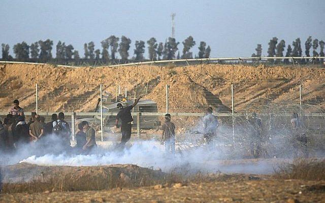Illustration. Des Palestiniens affrontent les soldats israéliens le long de la frontière entre la bande de Gaza et Israël, à l'est de   Khan Younis, dans le sud de Gaza (Crédit : AFP Photo/Said Khatib)