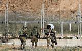 Des soldats israéliens emmènent un Palestinien blessé qui, selon l'armée, a tenté de franchir la barrière frontalière à l'est de Jabaliya, dans le nord de la bande de Gaza, le 27 juin 2018. (Crédit : Saïd Khatib/AFP)