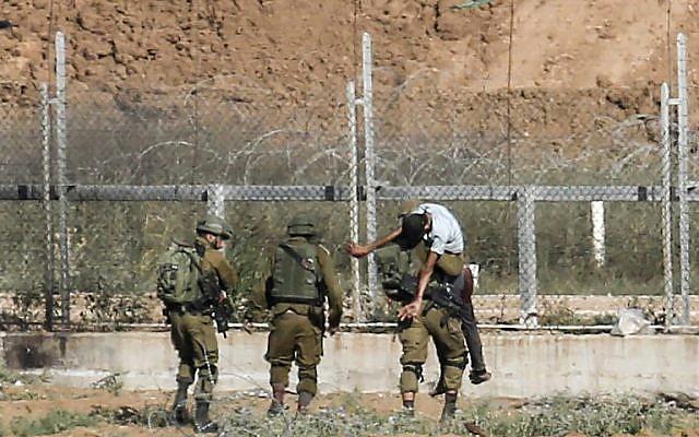 Les soldats israéliens emmènent un Palestinien blessé qui, selon l'armée, aurait tenté d'ouvrir une brèche dans la frontière à l'est de Jabaliya, dans le nord de la bande de Gaza, le 27 juin 2018 (Crédit : Said Khatib/AFP)