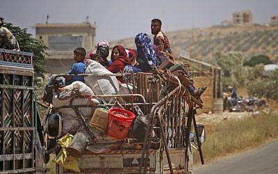 Des Syriens déplacés par les bombardements des forces gouvernementales dans la province de Daraa, dans le sud du pays, arrivent près de la municipalité de Shayyah, au sud de la ville de Daraa,  alors qu'ils se rendent à la zone frontalière entre le plateau du Golan occupé par Israël et la Syrie, le 29 juin 2018 (Crédit :. / AFP PHOTO / Mohamad ABAZEED