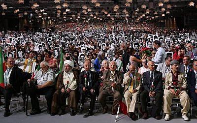 """Des gens tiennent des photos de proches tués par le régime iranien lors de l'événement """"Iran Libre - l'Alternative""""  à Villepinte, au nord de Paris, le 30 juin 2018 (Crédit : """"AFP Photo/Zakaria Abdelkafi)"""