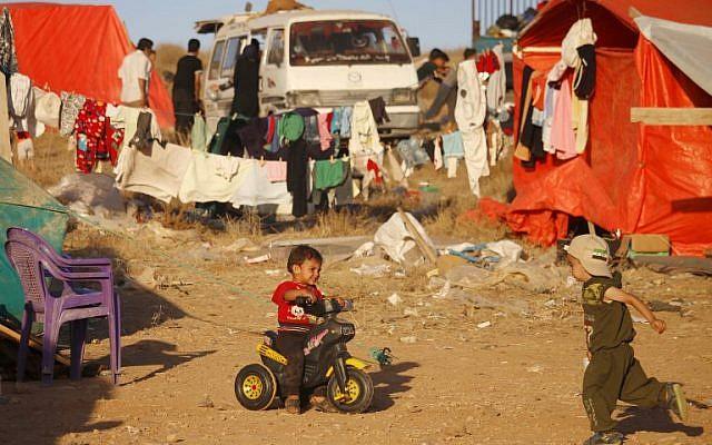 Des enfants syriens de la province de Deraa qui ont fui les bombardements de forces pro-gouvernementales attendent de pouvoir franchir la frontière jordanienne, à Nassib, le 1er juillet 2018. (Crédit : AFP / Mohamad ABAZEED)