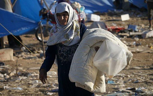 Des Syriens déplacés de la province de Daraa qui ont fui les frappes des forces pro-gouvernementales  dans un camp de fortune à proximité de la frontière jordanienne et de la ville de  Nasib, dans le sud de la Syrie, le 2 juillet 2018 (Crédit : AFP/Mohamad Abazeed)