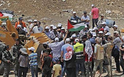 Des manifestants brandissent des drapeaux palestiniens alors qu'ils tentent d'empêcher un tracteur de paver une route d'accès au village bédouin de Khan al-Ahmar, en Cisjordanie, le 4 juillet 2018. (AFP Photo/Ahmad Gharabli)