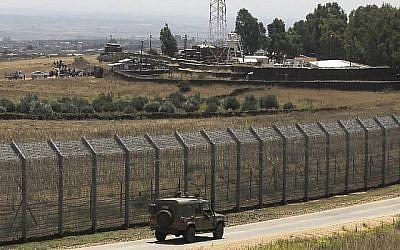 Une photo prise le 4 juillet 2018 depuis le plateau du Golan montre des Syriens déplacés de la province de Daraa qui organisent une manifestation (en haut à gauche) pour demander une protection internationale, dans le village syrien d'al-Rafid, près de la barrière frontalière avec Israël. (AFP/Jalaa Marey)