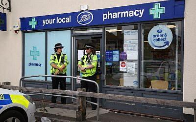 Des policiers devant une pharmacie à Amesbury, où deux personnes ont été retrouvée inconscientes, dans des circonstances encore floues d'un empoisonnement, le 4 juillet 2018. (Crédit : AFP / Geoff CADDICK)