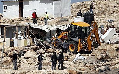 La police israélienne sécurise un bulldozer démolissant des installations dans le village bédouin d'Abu Nuwar, à l'est de Jérusalem, en Cisjordanie, le 4 juillet 2018. (AHMAD GHARABLI/AFP)