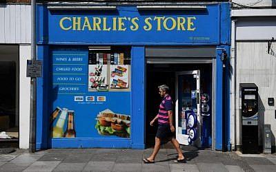 Un piéton passe devant un magasin de journaux, l'un des derniers endroits visités par Dawn Sturgess, âgée de 44 ans, avant de tomber malade le 30 juin à Salisbury, dans le sud de l'Angleterre, le 6 juillet 2018. (Crédit : AFP / Chris J Ratcliffe)