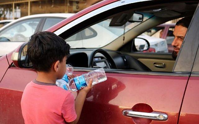 Un enfant irakien vend des bouteilles d'eau à des conducteurs circulant dans une rue de la ville de Mossoul, dans le nord de l'Irak, le 7 juillet 2018. (Crédit : AFP / Waleed AL-KHALID)