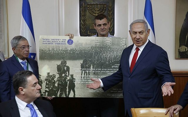 Le Premier ministre israélien Benjamin Netanyahu (d) reçoit un cadeau de l'Institut Zeev Jabotinsky lors de la réunion hebdomadaire du cabinet à Jérusalem, le 8 juillet 2018. (Crédit : AFP/POOL/ABIR SULTAN)