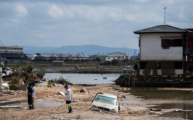 Des gens inspectent leurs maisons endommagées dans une zone touchée par les inondations à Mabi, dans la préfecture d'Okayama, le 10 juillet 2018. (Crédit : AFP / Martin BUREAU)