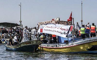 Des activistes escortent un bateau transportant des Palestiniens blessés lors d'affrontements le long de la barrière de sécurité de Gaza alors qu'il tente de franchir le blocus naval israélien du port de Gaza le 10 juillet 2018. (Crédit : Mahmud Hams / AFP)