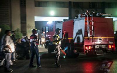 La police et les pompiers égyptiens devant un réservoir chimique après une explosion, près de l'aéroport du Cire, le 12 juillet 2018. (Crédit : AFP/ Khaled DESOUKI)