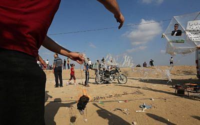 Un manifestant palestinien se prépare à  attacher un dispositif incendiaire à un cerf-volant avant de le lancer vers Israël à la frontière entre Israël et Gaza, le 13 juillet 2018 (Crédit : AFP PHOTO / MAHMUD HAMS)